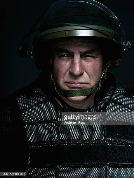 Mature man wearing bulletproof vest and helmet, portrait