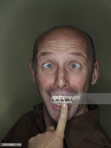 Mature man wearing fake teeth, making funny face, close-up, portrait