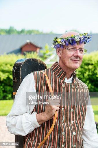 Mature man wearing flower wreath