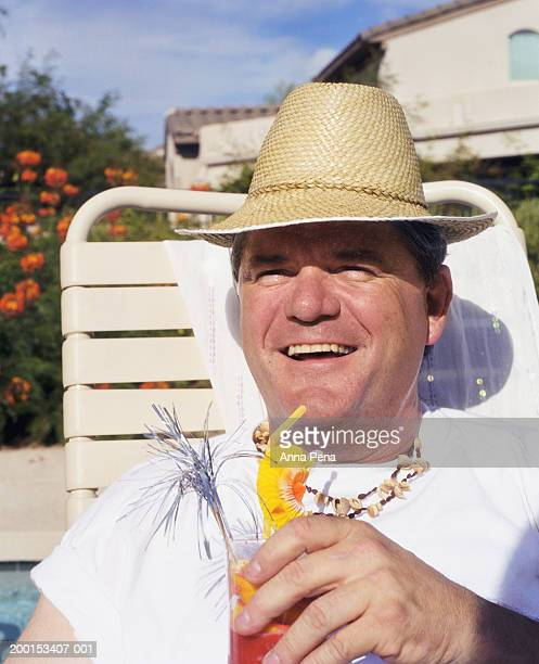 Mature man wearing hat and holding drink smiling, portrait