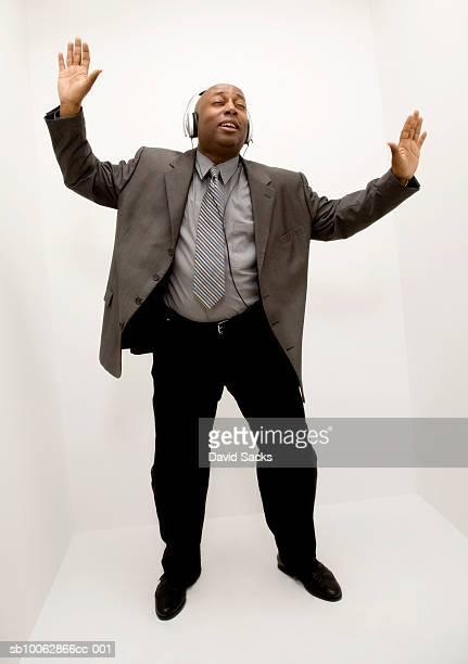Mature man wearing headphones and dancing in studio, high angle view