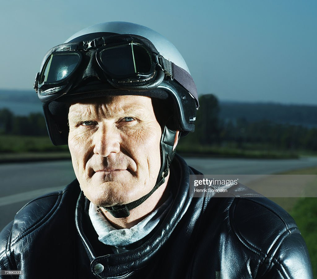 Mature man wearing motorcycle helmet, portrait : Stock Photo