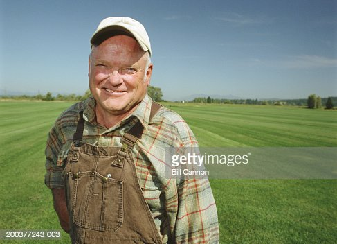 Mature man wearing overalls, smiling, portrait : Stock Photo