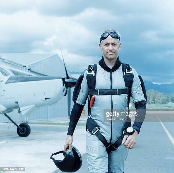 Mature man wearing parachute harness by plane, portrait