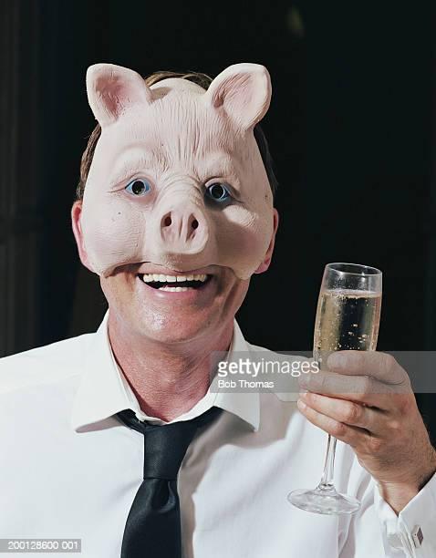 Mature man wearing pig mask, raising champagne flute, portrait