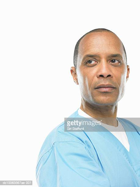 Mature man wearing scrubs looking away