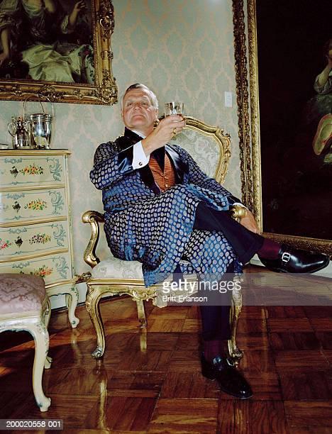 Mature man wearing smoking jacket raising glass, portrait