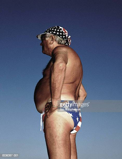 Mature man wearing 'Stars and Stripes' swimming trunks, profile