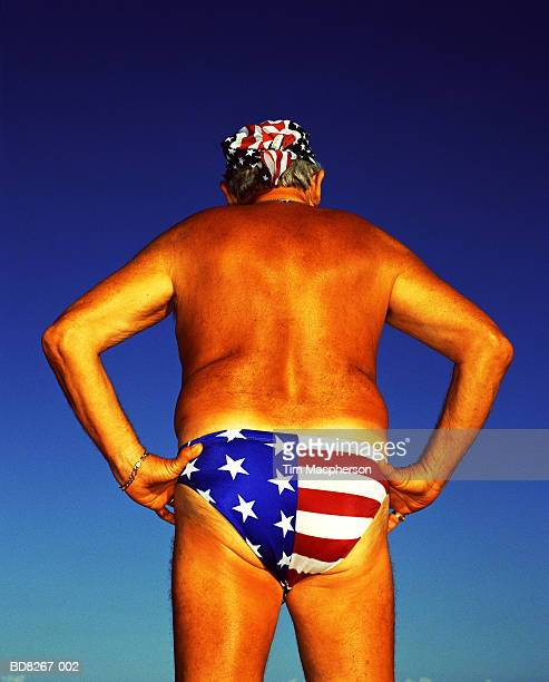 Mature man wearing 'Stars and Stripes' swimming trunks, rear view