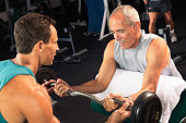 Mature man weight training with male fitness instructor
