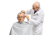 Mature man with a barber cutting his hair isolated on white background