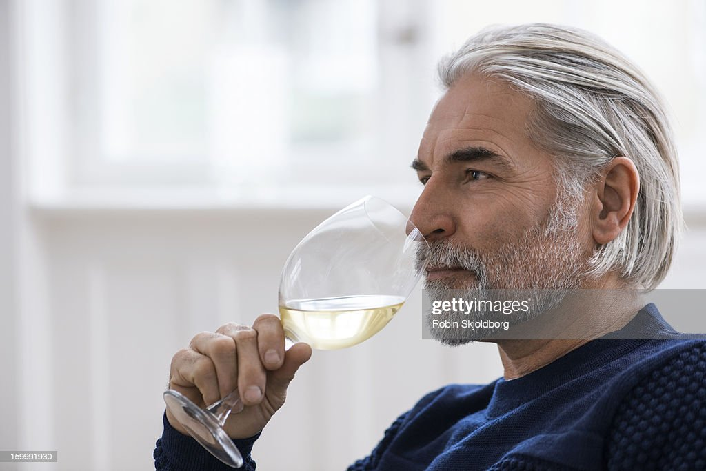 Mature man with a glass of white wine