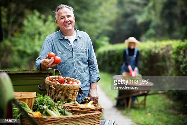 Reifer Mann mit Körbe von geerntetes Gemüse.