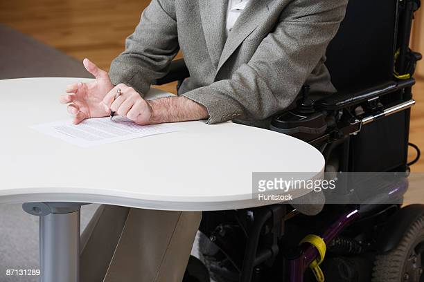 Mature man with cerebral palsy signing a document