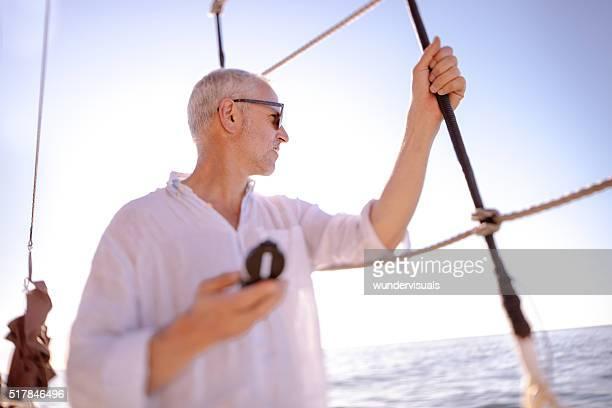 Homme d'âge mûr avec boussole regardant l'horizon depuis son Yacht