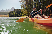 Portrait of a mature man with enjoying kayaking in a lake. Caucasian man wearing a cap paddling a kayak on summer day.