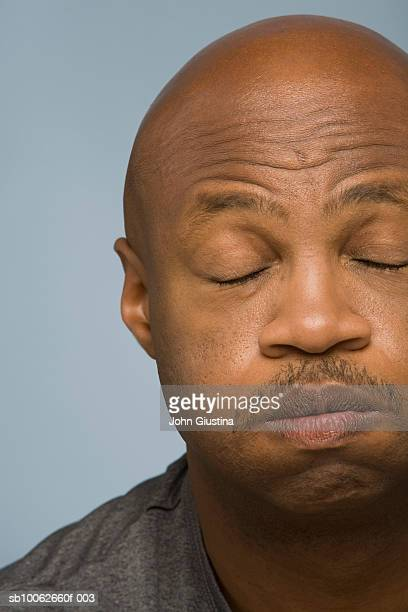 Mature man with eyes closed, blowing, close-up