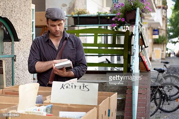 mature man with flat cap looks books in flea market