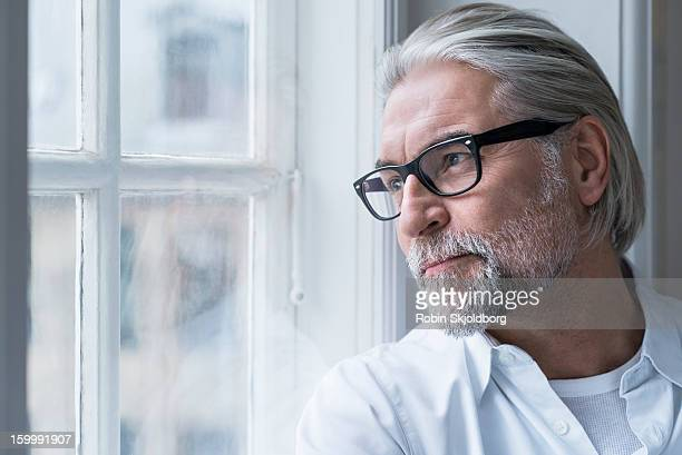 Mature man with glasses looking out of window