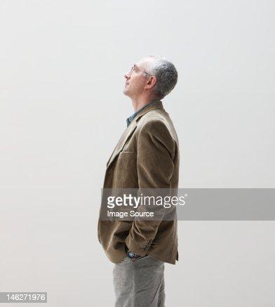 Mature man with hands in pocket looking up, studio shot