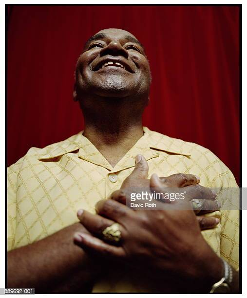 Mature man with hands over heart, smiling, low angle view