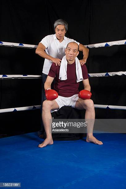 Mature man with his coach at the corner in a boxing ring