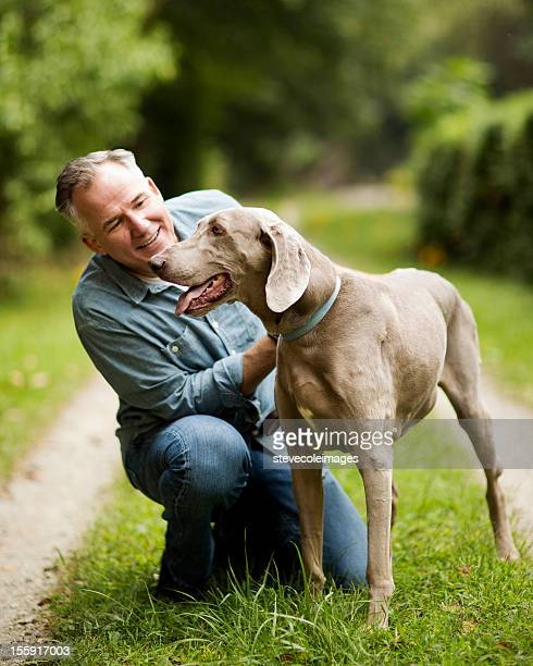 Mature Man With His Dog In Park.