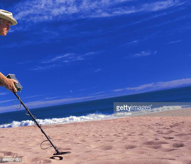 Mature man with metal detector on beach (Digital Enhancement)
