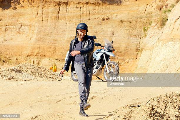 Mature man with motor bike in sand pit