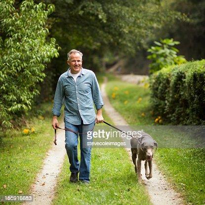 Mature Man With Pet Dog At Park.
