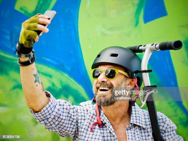 Mature man with scooter - graffiti on background