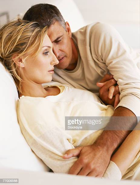 Mature man with woman sitting on sofa, side view