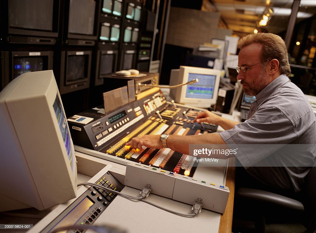 Mature man working at mixing console in television studio