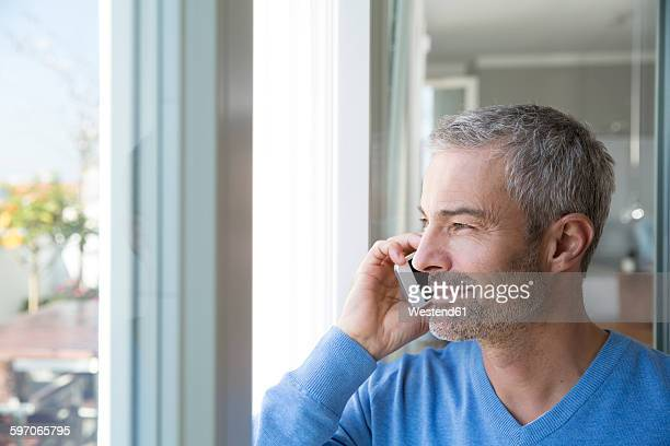 Mature man working from home using smart phone