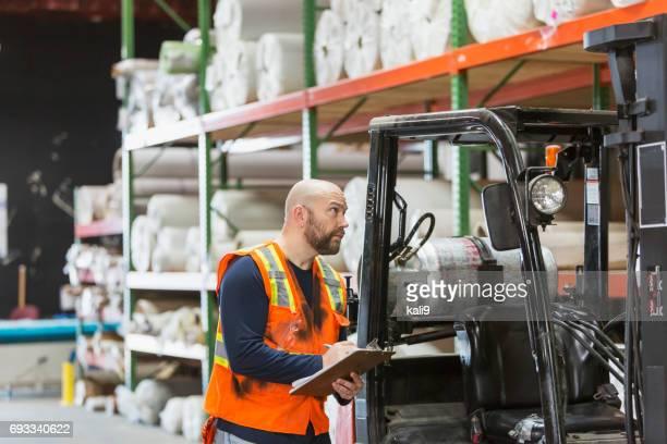 Mature man working in carpet warehouse