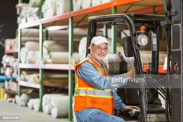 Mature man working in carpet warehouse with forklift