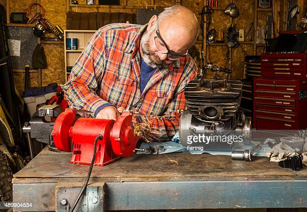 Mature man working in the garage on a motorcycle engine