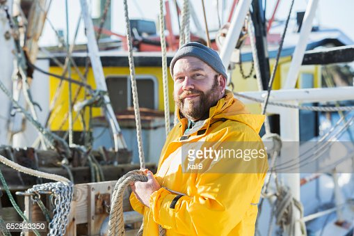 Mature man working on commercial fishing boat : Stock Photo