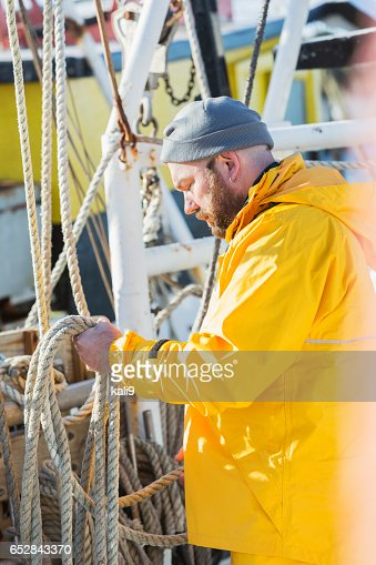 Mature man working on commercial fishing boat : Photo