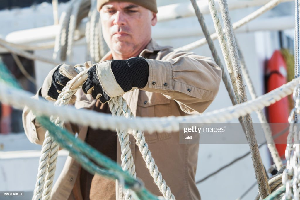 Mature man working on commercial fishing boat : Bildbanksbilder