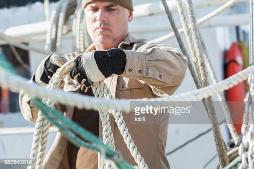 Mature man working on commercial fishing boat : Stock-Foto