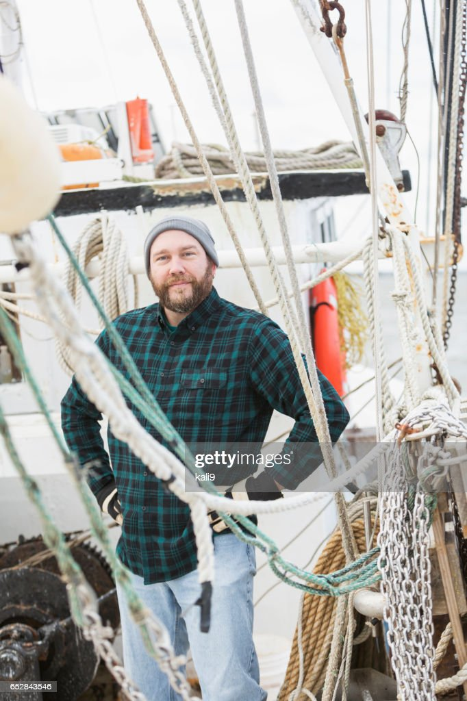 Mature man working on commercial fishing boat : Stockfoto