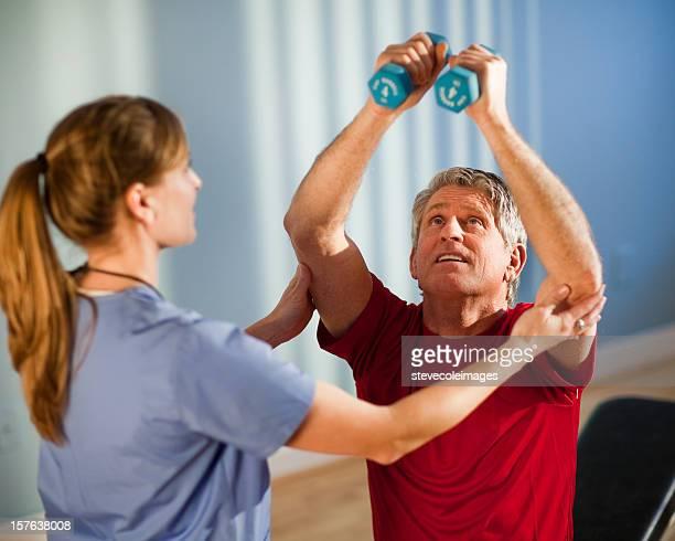 Homem maduro, trabalhando com uma Fisioterapeuta