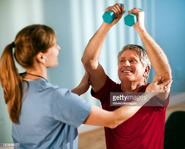 Mature Man Working With Female Physical Therapist