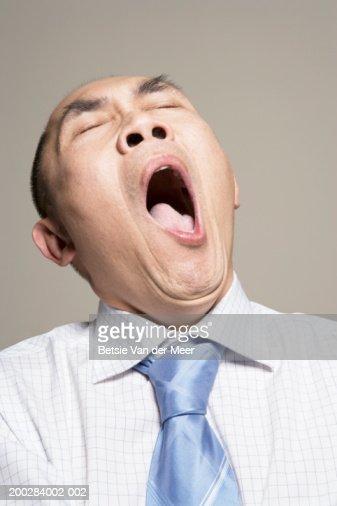 Mature man yawning, eyes closed, close-up