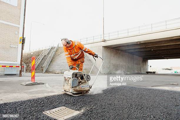 Mature manual worker laying asphalt at road construction site