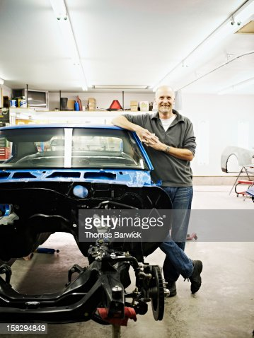Mature mechanic in garage with car restoration : Stock Photo