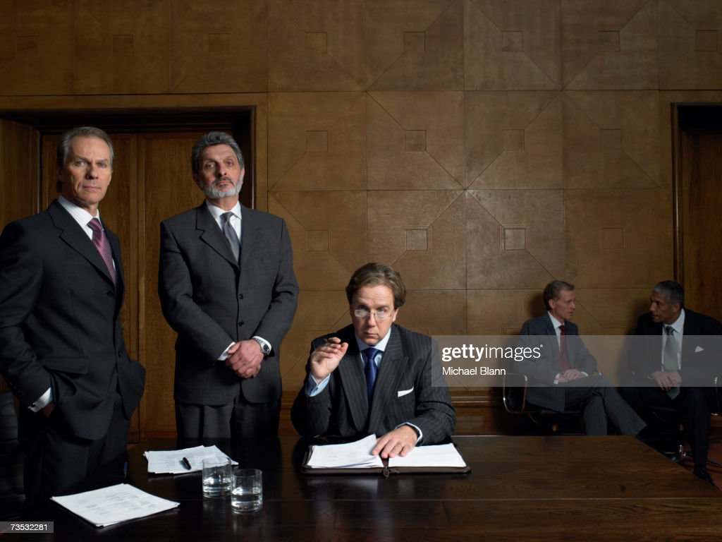 Mature men at end of table in conference room, portrait
