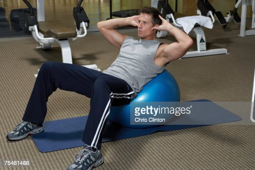 Mature men doing exercise on fitness ball in gym : Stock Photo