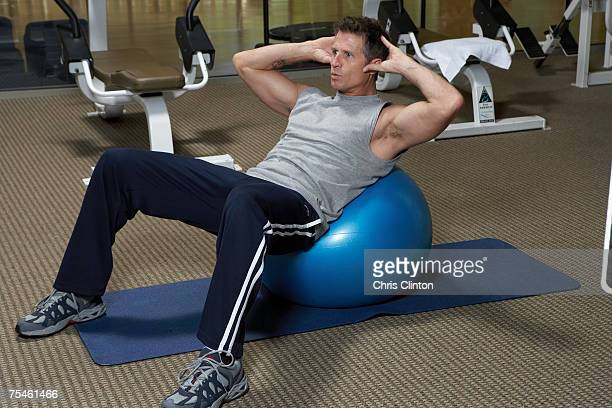 Mature men doing exercise on fitness ball in gym
